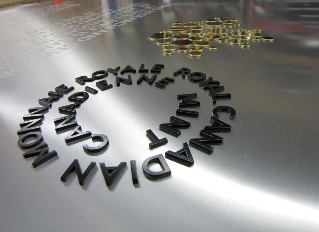 plaque commémorative - aluminium et laiton - Monnaie royale canadienne détail du lettrage